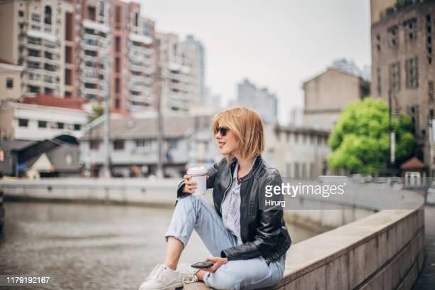 café takeaway da terra arrendada da mulher nova e telefone móvel - jeans calça comprida - fotografias e filmes do acervo