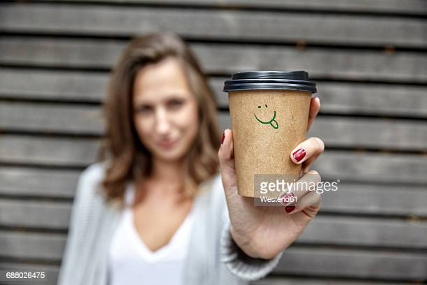 young woman holding takeaway coffee cup with smiley face - kaffee getränk stock-fotos und bilder