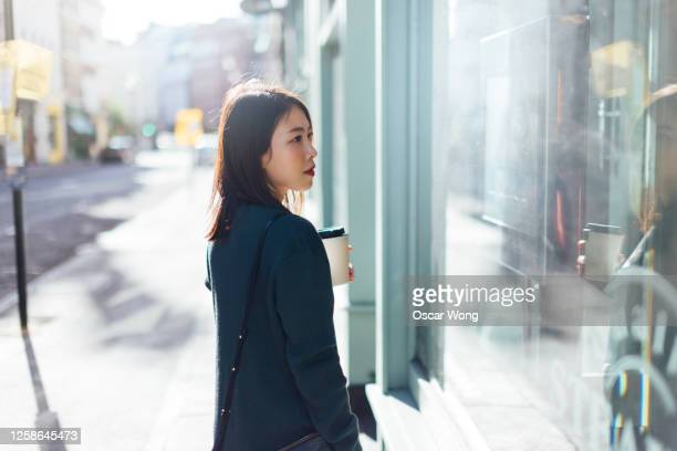 young woman holding take-away coffee while shopping on the high street - merchandise stock pictures, royalty-free photos & images
