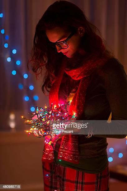 Young woman holding tangle of christmas lights