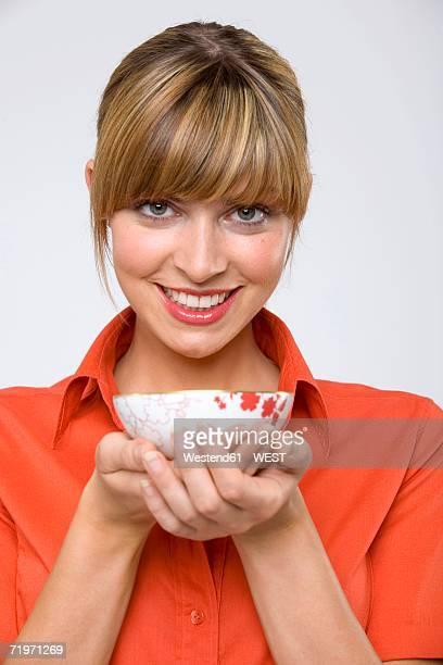 Young woman holding tea bowl, smiling, portrait