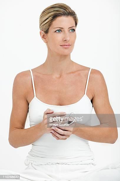 jeune femme tenant teacup-expression anglo-saxonne - débardeur photos et images de collection