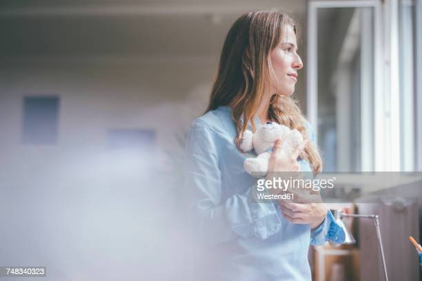 young woman holding teddy looking out of the window - desiderio foto e immagini stock