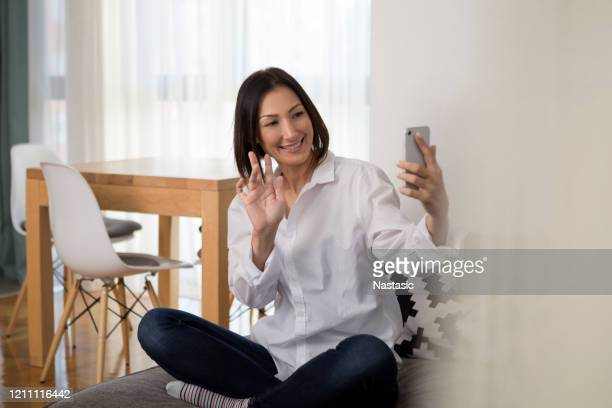 young woman holding telephone making skype conversation waving - photo messaging stock pictures, royalty-free photos & images