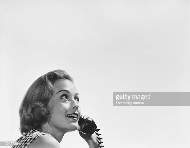Young woman holding telephone receiver, smiling