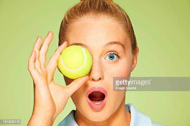 Young woman holding tennis ball over her eye