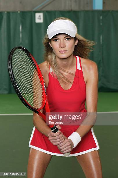 Young woman holding tennis racket, portrait