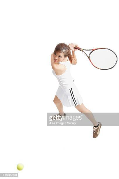 Young woman holding tennis racket, waiting for ball