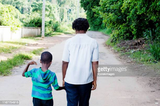young woman holding the hand of her  child and walk on the country road. - côte d'ivoire stock pictures, royalty-free photos & images