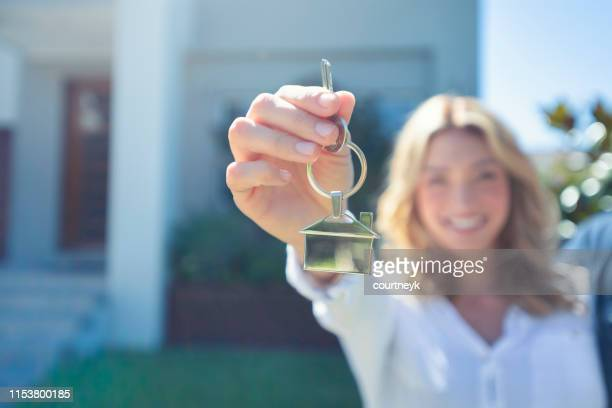 young woman holding the key to her new house. - home ownership stock pictures, royalty-free photos & images