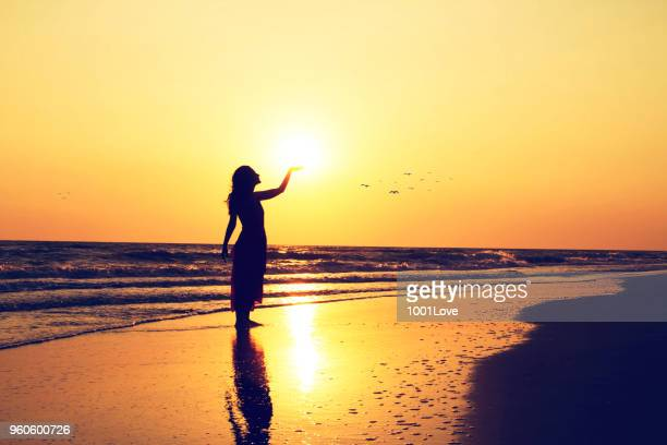 Young woman holding the sun at beach. Freedom concept. Elegance at sunset.