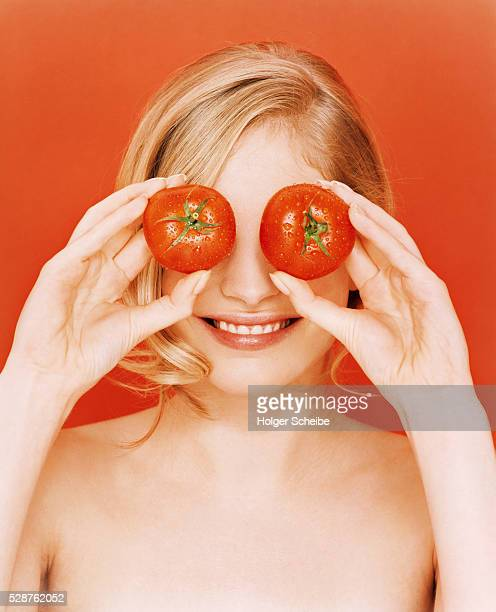 Young woman holding tomatoes in front of her eyes