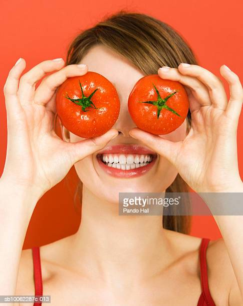 Young woman holding tomatoes over eyes, smiling, close-up