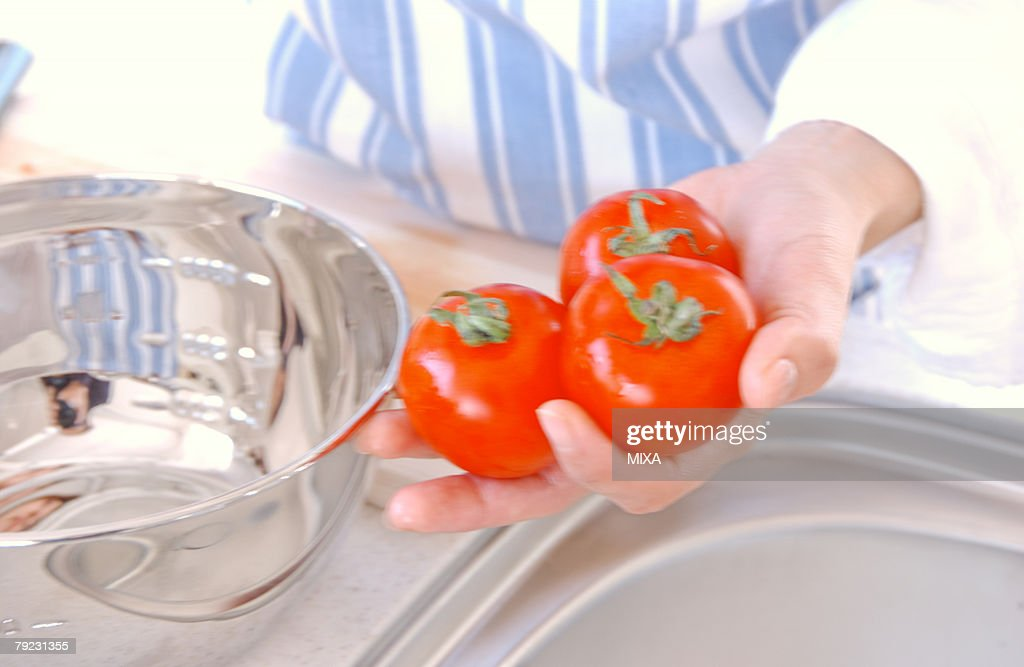 A young woman holding tomatoes : Stock Photo