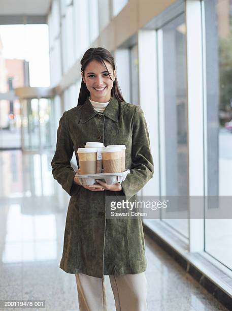 Young woman holding tray of coffee, portrait