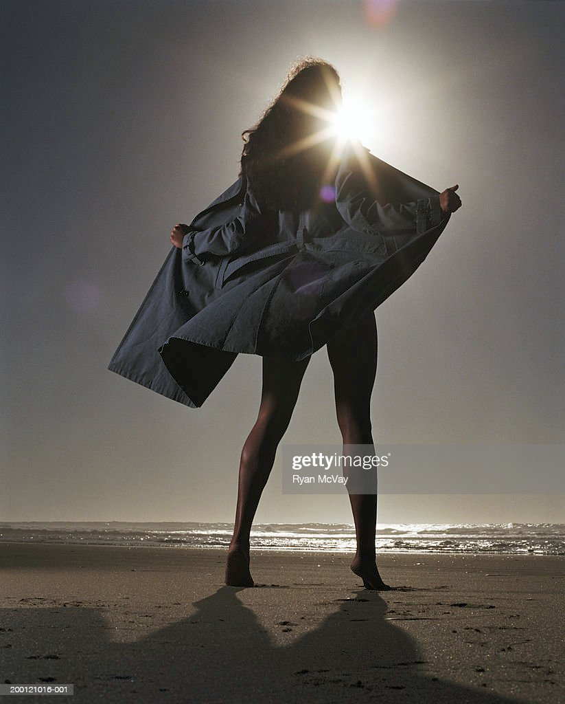 Young woman holding trench coat open on beach, rear view : Stock Photo