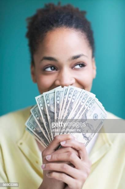 Young woman holding twenty dollar bills