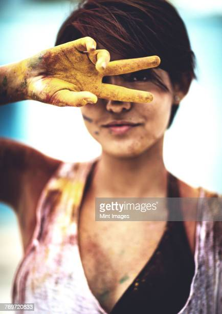 Young woman holding two paint-stained fingers in front of her face, looking at camera. Paint covered clothes and skin.