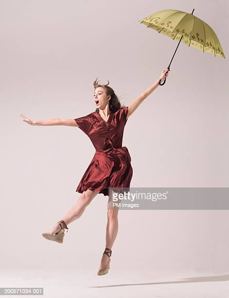 young woman holding umbrella and blowing in wind - fliegen stock-fotos und bilder