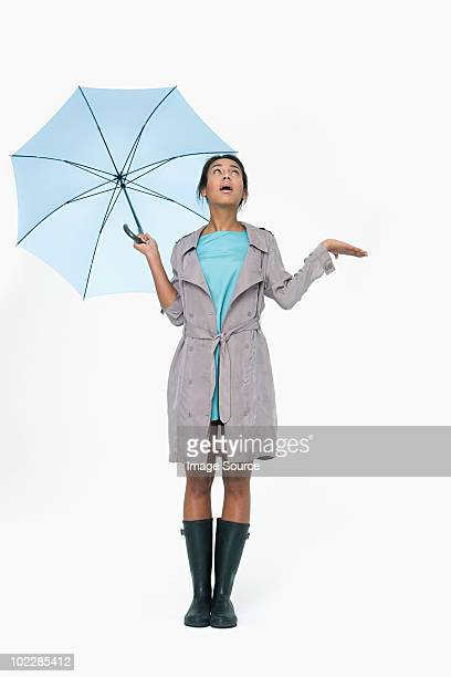 Young woman holding umbrella and looking up