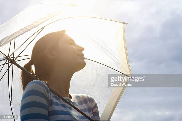 Young woman holding umbrella in burst of sunlight.