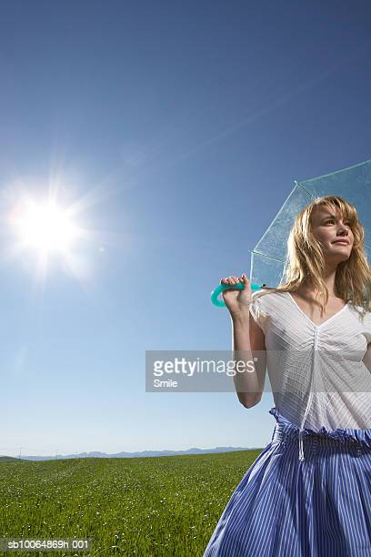 Young woman holding umbrella in field, looking away