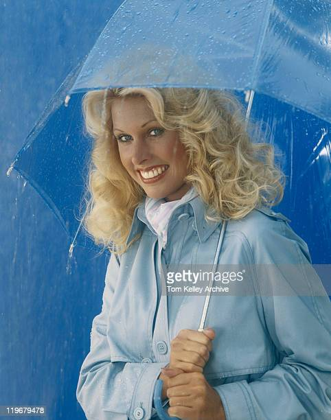 Young woman holding umbrella in rain, smiling, portrait