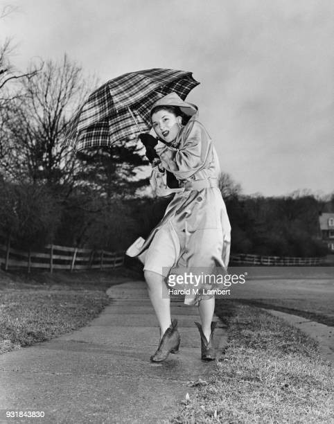 young woman holding umbrella on rainy day - vintage raincoat stock photos and pictures