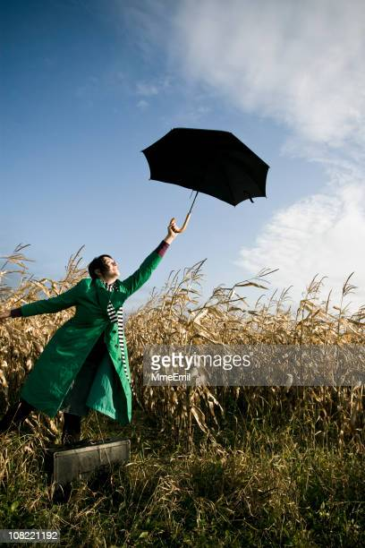 Young Woman Holding Umbrella Up and Standing in Corn Field