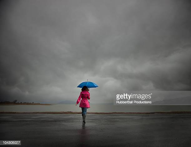Mujer joven sosteniendo pie paraguas en dirección al lago