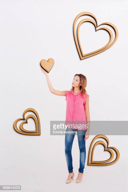 Young woman holding up a heart
