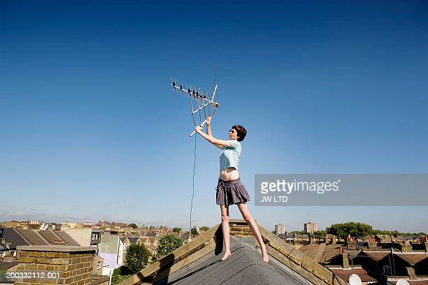 young woman holding up aerial on rooftop - adjusting stock pictures, royalty-free photos & images