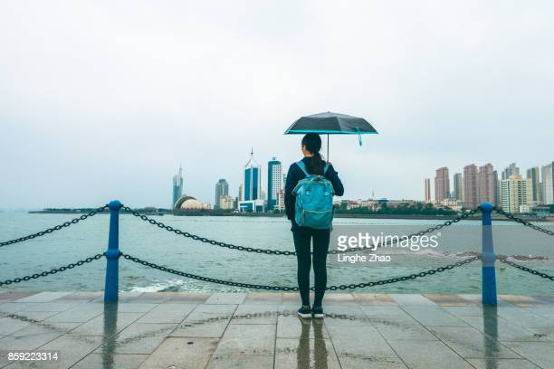Young woman holding up an umbrella by sea