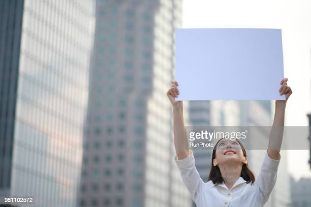 young woman holding up blank sign - blank sign stock photos and pictures