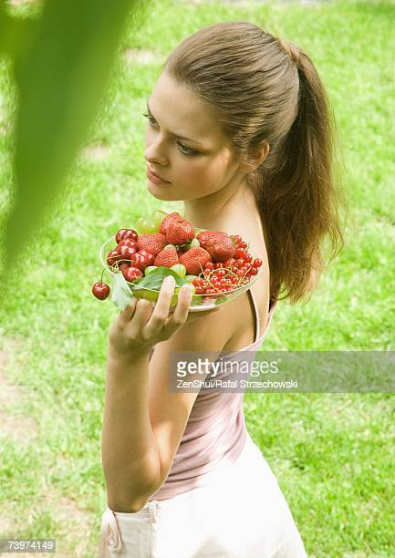 Young woman holding up bowl of fruit