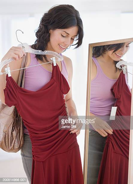 Young woman holding up dress in front of mirror.