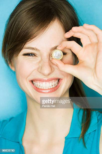 Young woman holding up Euro coin over eye, smiling
