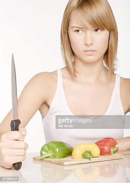 Young woman holding up knife in front of bell peppers