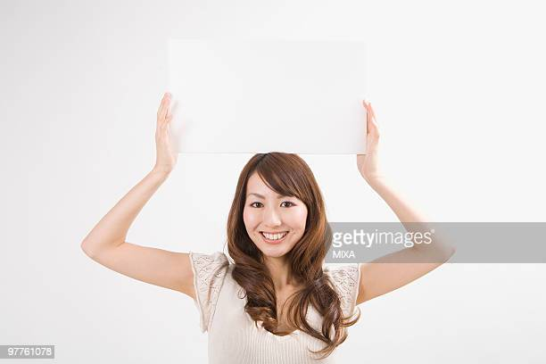 Young woman holding up message board
