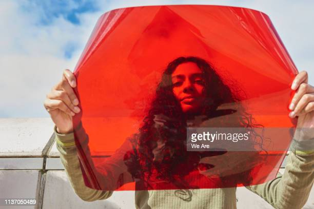 young woman holding up red filter in front of face - rébellion photos et images de collection