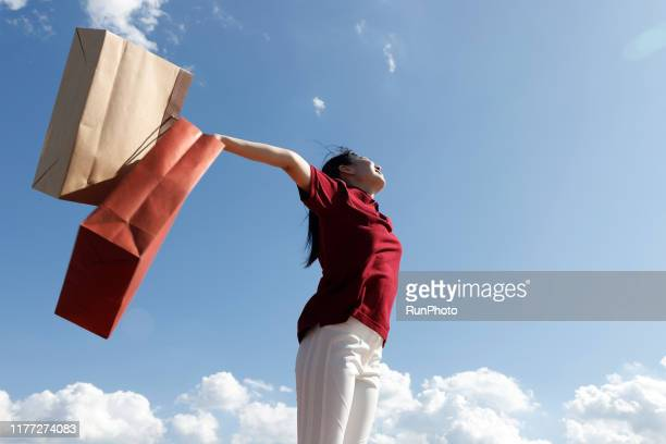 young woman holding up shopping bags against sky - 余暇 ストックフォトと画像