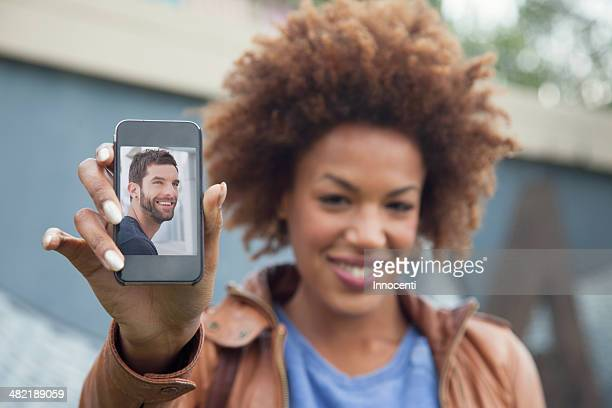 Young woman holding up smartphone with photograph of boyfriend
