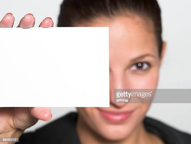 Young woman holding up white paper card