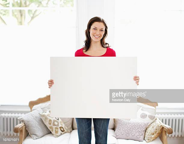 Young woman holding up whiteboard