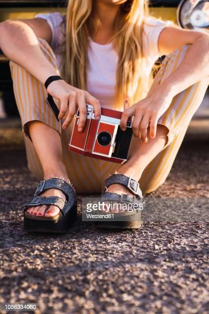 young woman holding vintage camera sitting outside at a van - sandalia fotografías e imágenes de stock