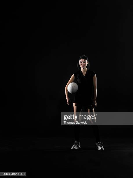 Young woman holding volleyball, portrait
