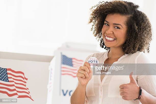 young woman holding voting badge and smiling - election day stock photos and pictures
