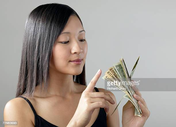 young woman holding wad of dollar bills, counting the money - richard drury stock pictures, royalty-free photos & images