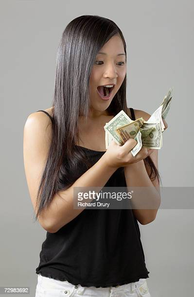 young woman holding wad of dollar bills to face with excited expression - richard drury stock pictures, royalty-free photos & images