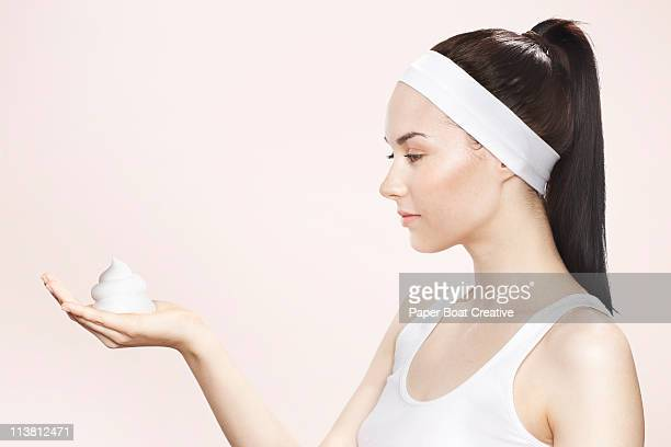 Young woman holding washing foam in her hands